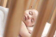 Bebé que duerme en un pesebre Fotografía de archivo libre de regalías