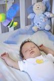 Bebé que duerme pacífico en su pesebre Fotografía de archivo