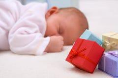 Bebé que duerme por los rectángulos de regalo Imagen de archivo libre de regalías
