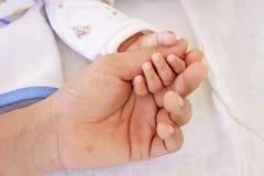 Bebé que duerme y que lleva a cabo la mano con la mano del padre Imágenes de archivo libres de regalías