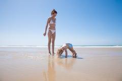Bebé que empuja-para arriba en la costa con la madre Imagenes de archivo