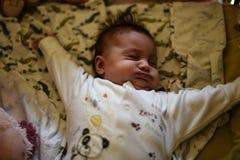 Bebé que estira en pesebre imagen de archivo
