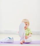 Bebé que golpea con el pie en cámara con las zapatillas de deporte grandes Imagenes de archivo