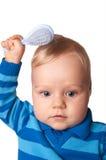 Bebé que intenta aplicar su pelo con brocha fotos de archivo