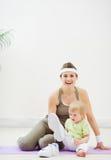 Bebé que intenta desgastar las zapatillas de deporte de las madres Foto de archivo