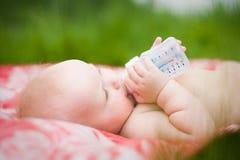 Bebé que introduce con la botella Imagen de archivo