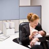 Bebé que introduce de la empresaria en el escritorio Imagen de archivo libre de regalías