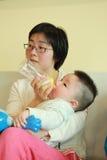 Bebé que introduce de la madre Foto de archivo