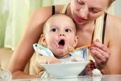 Bebé que introduce de la madre con la cuchara Fotos de archivo