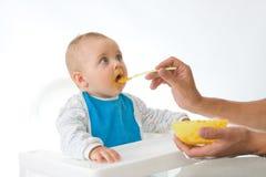 Bebé que introduce del hombre con una cuchara Fotografía de archivo libre de regalías