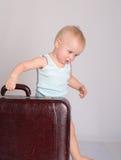 Bebé que joga com a mala de viagem no fundo cinzento Imagens de Stock