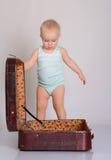 Bebé que joga com a mala de viagem no fundo cinzento Foto de Stock Royalty Free