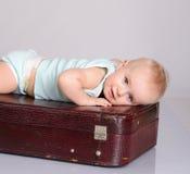Bebé que joga com a mala de viagem no fundo cinzento Imagem de Stock