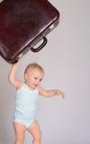 Bebé que joga com a mala de viagem no fundo cinzento Fotos de Stock
