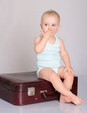 Bebé que joga com a mala de viagem no fundo cinzento Fotos de Stock Royalty Free