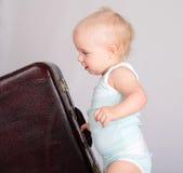 Bebé que joga com a mala de viagem no fundo cinzento Fotografia de Stock Royalty Free