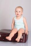 Bebé que joga com a mala de viagem no fundo cinzento Imagens de Stock Royalty Free