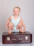 Bebé que joga com a mala de viagem no fundo cinzento Imagem de Stock Royalty Free