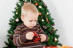 Bebé que joga com um brinquedo no Natal Imagem de Stock