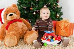 Bebé que joga com um brinquedo no Natal Fotos de Stock Royalty Free