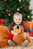 Bebé que joga com um urso de peluche no Natal Fotografia de Stock Royalty Free