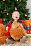Bebé que joga com um urso de peluche no Natal foto de stock