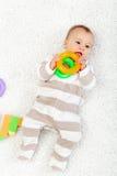 Bebé que joga no assoalho que mastiga brinquedos fotografia de stock