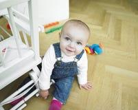 Bebé que juega cerca de silla Fotos de archivo libres de regalías