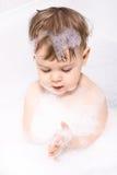 Bebé que juega con champú Imágenes de archivo libres de regalías