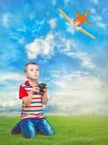 Bebé que juega con el aeroplano en el control en el césped verde foto de archivo