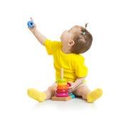 Bebé que juega con el juguete colorido y que mira para arriba Fotos de archivo libres de regalías