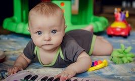 Bebé que juega con el juguete del piano Foto de archivo