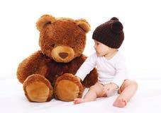 Bebé que juega con el juguete grande del oso de peluche en blanco Fotos de archivo libres de regalías