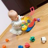 Bebé que juega con el juguete plástico