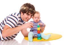 Bebé que juega con el padre Fotografía de archivo libre de regalías