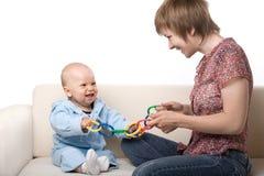 Bebé que juega con la madre Imagen de archivo