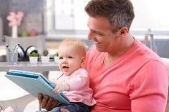 Bebé que juega con la tablilla Imagen de archivo