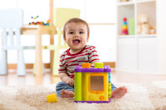 Bebé que juega con los juguetes coloridos en casa Siete meses felices el jugar y descubrimiento infantiles del niño Fotos de archivo libres de regalías