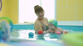 Bebé que juega con los juguetes en la lección de la natación del bebé almacen de video