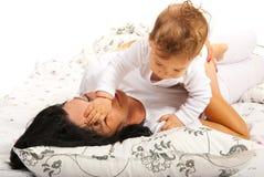 Bebé que juega con su cara de la madre Fotos de archivo