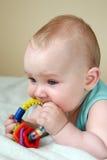Bebé que juega con traqueteo Imagenes de archivo