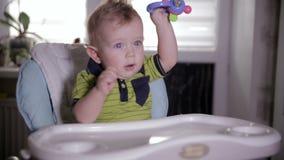 Bebé que juega con un juguete, sentándose en una silla del bebé Un bebé de los años almacen de metraje de vídeo