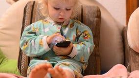 Bebé que juega con un teléfono almacen de metraje de vídeo