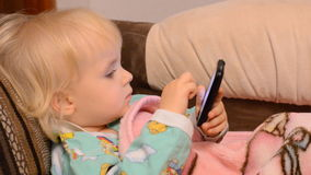 Bebé que juega con un teléfono metrajes
