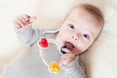 Bebé que juega con un traqueteo Imagen de archivo