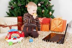 Bebé que juega con una computadora portátil y los juguetes en el christm Imágenes de archivo libres de regalías
