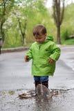 Bebé que juega en charcos Imagen de archivo libre de regalías