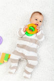 Bebé que juega en el suelo que mastica los juguetes Fotografía de archivo