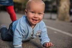 Bebé que juega en la calle y la sonrisa Imagen de archivo libre de regalías