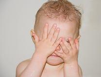 Bebé que juega ojeada un abucheo en baño imagen de archivo
